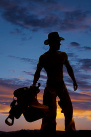 picture of western saddle  - A silhouette of a cowboy looking to the side holding on to his saddle - JPG