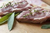 picture of salvia  - Raw pork steaks with salvia leaves and thyme branches - JPG