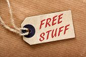 image of enticing  - The phrase Free Stuff on a brown paper luggage tag on a brown wrapping paper background - JPG