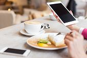 pic of cafe  - Woman using tablet computer while sitting in cafe - JPG