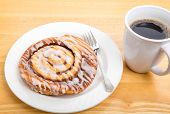 stock photo of cinnamon  - A fresh cinnamon roll on a plate with fork and a cup of coffee - JPG