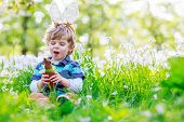stock photo of bunny ears  - Cute happy little boy wearing Easter bunny ears at spring green grass and blooming apple garden eating chocolate bunny and having fun outdoors - JPG