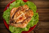 foto of bondage  - Bondage shibari roasted chicken with salad leaves on red plate on wooden background top view horizontal selective focus - JPG