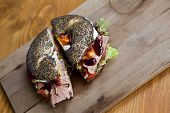 picture of bagel  - Bagel with ham salad and cream on a wooden table - JPG