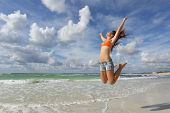 stock photo of cloudy  - Happy girl wearing bikini jumping on the beach on holidays with a cloudy sky in the background - JPG
