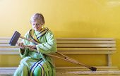 stock photo of hospital gown  - Senior woman injured sitting in the hallway of hospital holding crutches - JPG