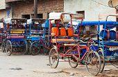 stock photo of rickshaw  - Many bicycle rickshaws on parking in Vrindavan - JPG