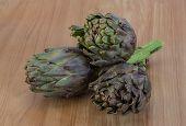 image of artichoke hearts  - Fresh Raw artichokes on the wooden background - JPG