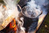 stock photo of bonfire  - Bonfire with smoke over metal old black boiling teapot - JPG
