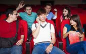 picture of disrespect  - Young men talking on the phone while watching movie at the cinema - JPG