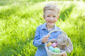image of easter eggs bunny  - smiling cheerful little boy holding basket with colorful easter eggs and bunny toy at spring time in the park - JPG