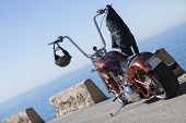 pic of chopper  - customized chopper motorcycle with a helmet and a leather black jacket hanging on the handlebar over a sea and sky background at sunrise - focus on the helmet