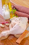 stock photo of gobbler  - raw chicken leg with spice on the board - JPG