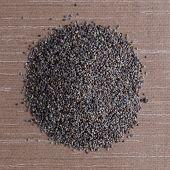 stock photo of opiate  - Top view of poppy seeds against brown vinyl background - JPG