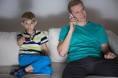 stock photo of people talking phone  - Young father talking the phone during son watching television - JPG