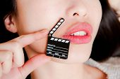 picture of clapper board  - Face detail of sensual woman lips no eyes with hand holding little movie clapper board - JPG