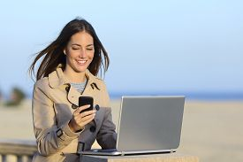 foto of self-employment  - Self employed woman working outdoors on the phone with a beach in the background - JPG