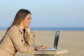 image of self-employment  - Side view of a self employed woman working with a laptop on the beach - JPG