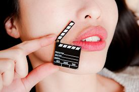 picture of x-rated  - Face detail of sensual woman lips no eyes with hand holding little movie clapper board - JPG
