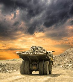 stock photo of dump_truck  - Heavy dump truck carrying the iron ore on the opencast mining on sunset - JPG