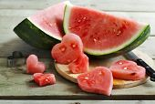 foto of watermelon slices  - Watermelon Slices on wooden table. Watermelon cut in the shape of hearts ** Note: Shallow depth of field - JPG