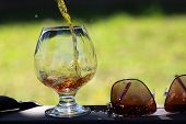 image of alcoholic beverage  - Amber alcoholic beverage poured in bocal stnading on table near sunglasses on natural background horizontal picture - JPG