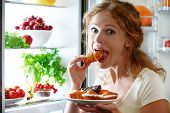 picture of refrigerator  - woman eats sweets at night to sneak in a refrigerator - JPG