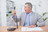 image of unnerving  - Irritated businessman answering phone in his office - JPG