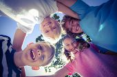 picture of huddle  - Smiling children forming a huddle in circle in the park - JPG