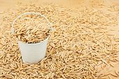 stock photo of bucket  - White bucket with grain oat on the wooden floor as a background - JPG