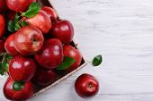 foto of wooden crate  - Ripe red apples in crate on wooden background - JPG
