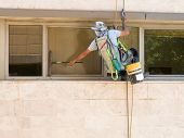 image of window washing  - Professional window washer cleaning windows on a building - JPG