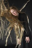 stock photo of hair blowing  - Smiling Blond Woman Wearing Black Dress Standing in Studio with Black Background with Long Hair Blowing in Strong Wind - JPG