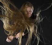 pic of hair blowing  - Mysterious Looking Blond Woman Wearing Black Dress Standing in Studio with Black Background with Long Hair Blowing in Strong Wind - JPG