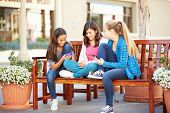 stock photo of tweeny  - Group Of Girls Sitting In Mall Using Mobile Phones - JPG