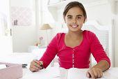foto of homework  - Young Girl Doing Homework At Desk In Bedroom - JPG