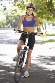 picture of riding-crop  - Woman Cycling Through Park - JPG
