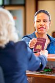 foto of receptionist  - Receptionist hands over a passport to a tourist at te front desk and reception of a hostel - JPG