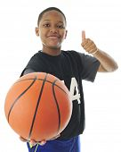 picture of preteen  - A preteen boy looking at and holding out his basketball for the viewer with a smile and a thumb - JPG