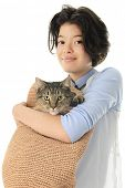 foto of tabby-cat  - A young teen girl happily holding her pet Tabby cat in a tan - JPG