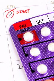 stock photo of contraception  - Colorful oral contraceptive pill on Gynecologist Desk - JPG