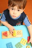 image of child development  - The child is keen collecting logic game