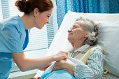 stock photo of nurse  - Nurse cares for a elderly woman lying in bed - JPG