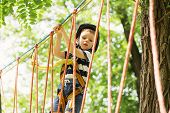 Постер, плакат: Kids Climbing In Adventure Park Boy Enjoys Climbing In The Ropes Course Adventure