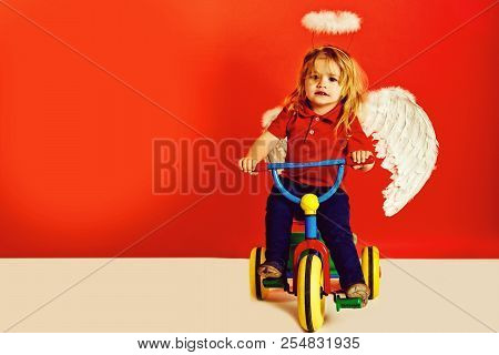 poster of Angel Boy On Red Background For Valentine Greeting, Beautiful Cupid On Bike With Blonde Hair And Hal