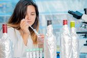 Young female technician in the quality control laboratory of wine quality inspection poster