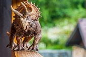 Dinosaur Toy Triceratops Strolls Along The Terrace. Walking The Dinosaur On The Railing. poster