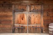 Old Wooden Double Doors With Rusty Weathered Hardware, Wooden Barrels Stacked Beside Door. Close Up. poster