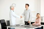 Male doctor consulting young couple in clinic poster