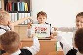 Little boy holding sign with words Stop bullying in classroom poster
